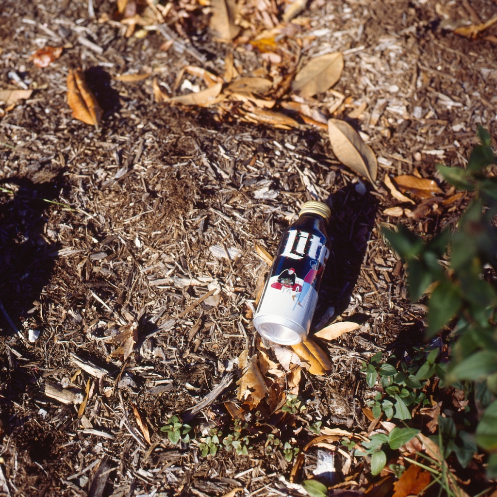 An empty Miller Lite beer can with Christmas label sits among the dead leaves on the ground