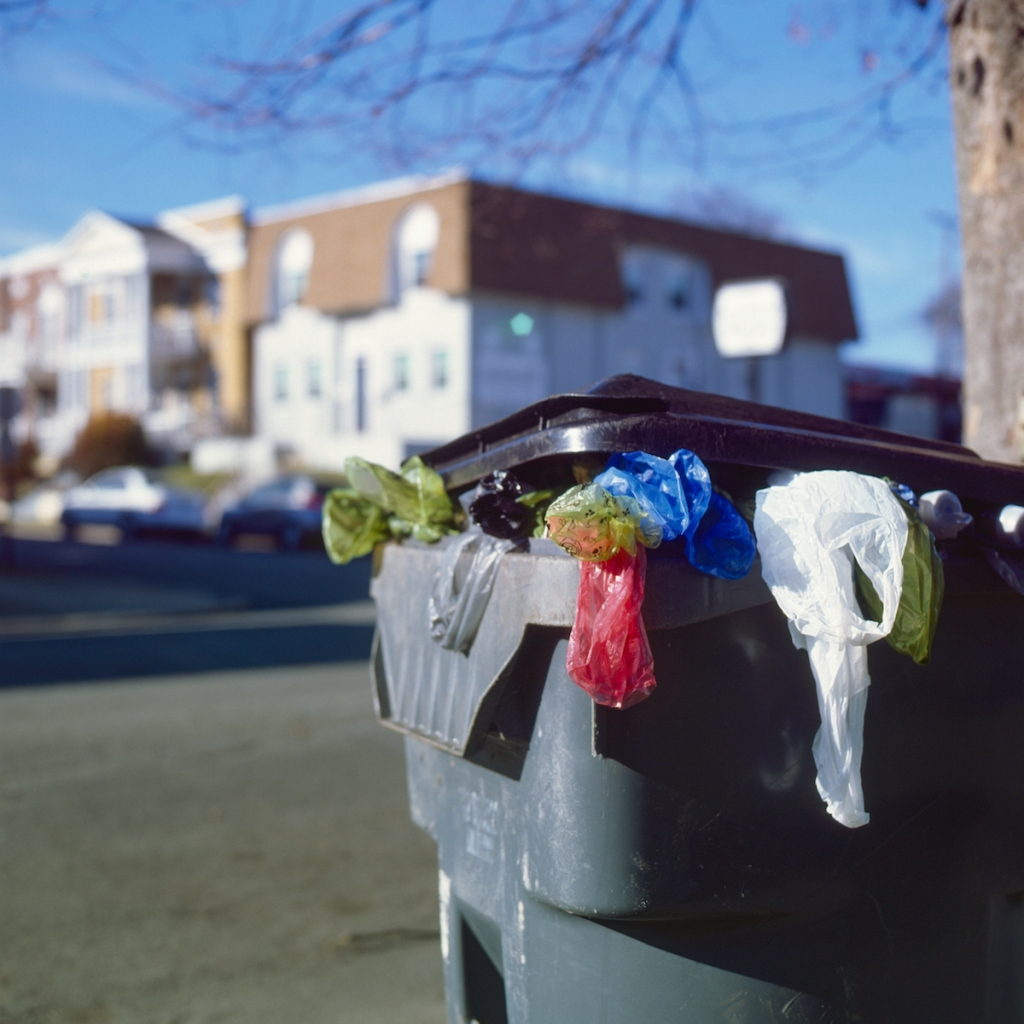 colorful trash bags hang out of an overstuffed city trashcan