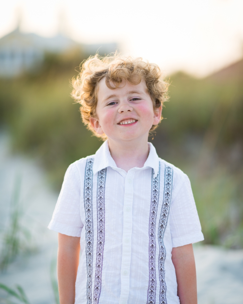 My son Wilson smiles while he stands in front of sand dunes in Myrtle Beach, SC
