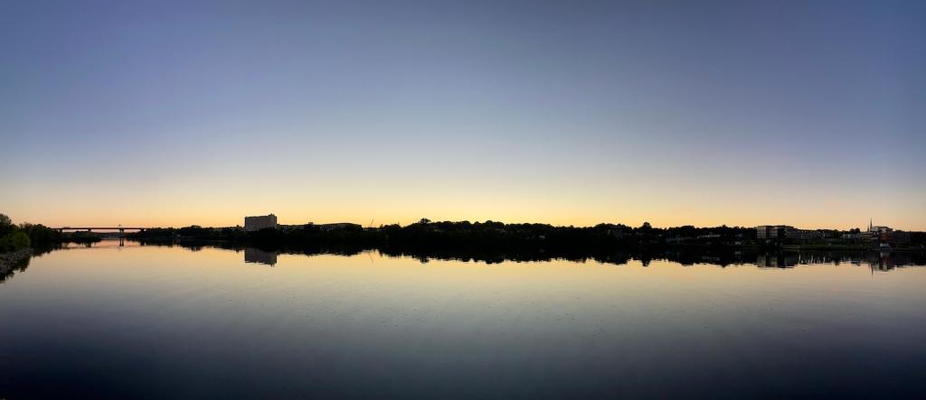 Panoramic view of Bangor at dusk across the Penobscot River.