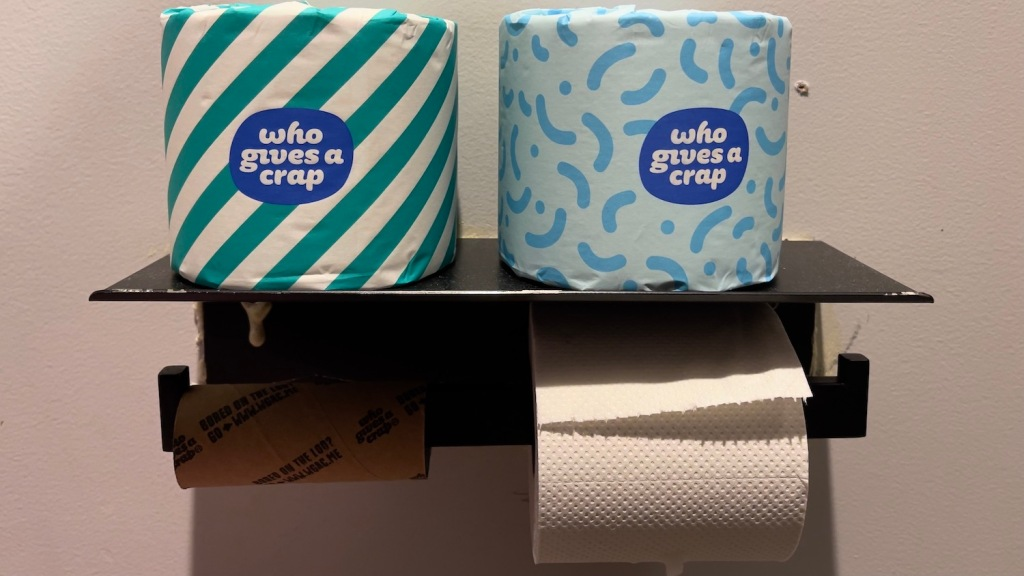 """Toilet paper in a bathroom with the label """"Who Gives a Crap"""""""