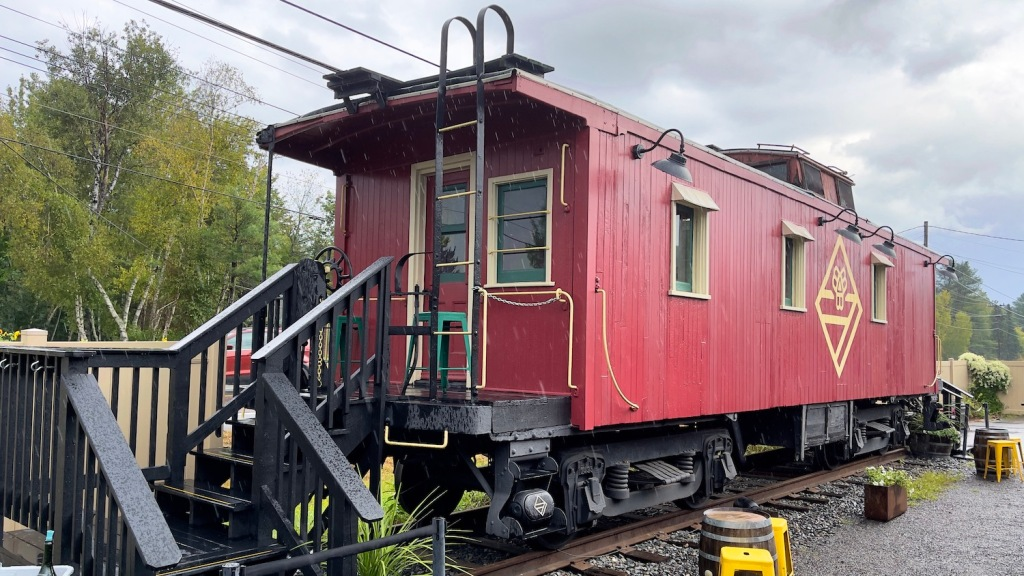Railroad caboose on display with rain pouring down at Bissell Brothers in Milo, ME.
