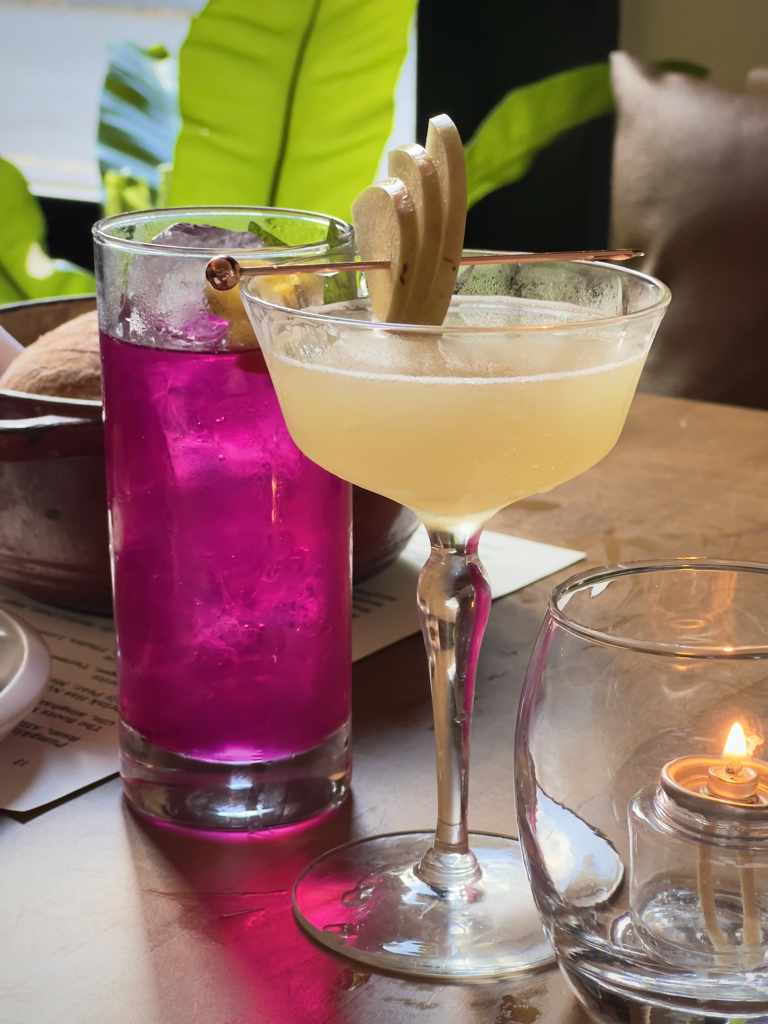 a cocktail and a prickly pear soda on a table at Chasing Sage restaurant in Charleston, SC