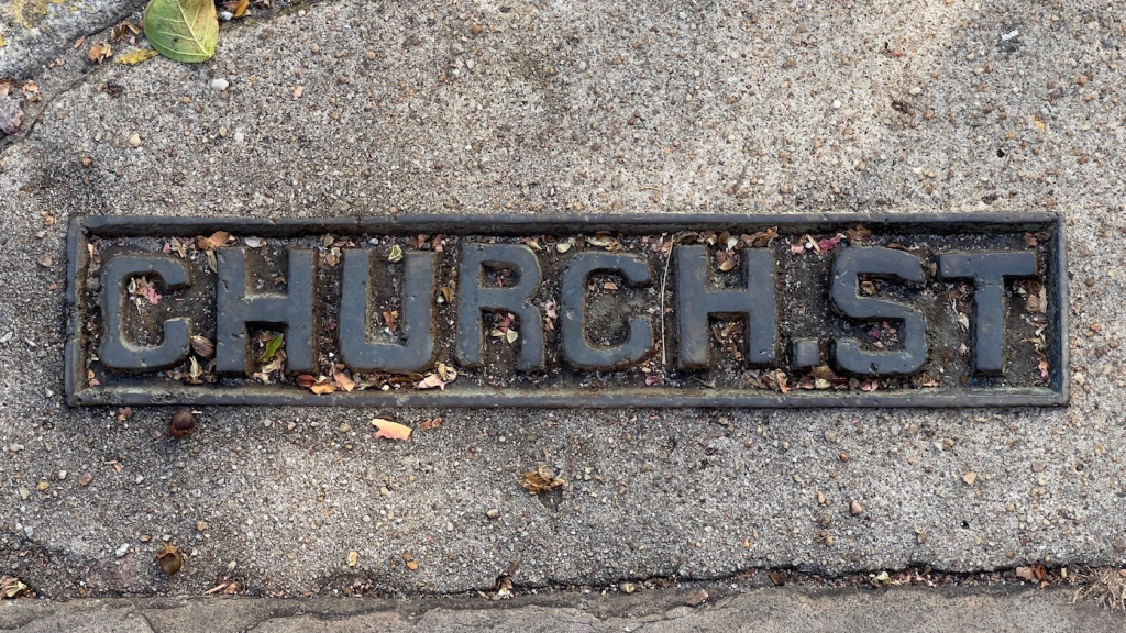 Metal Church Street sign stamped into the sidewalk in Charleston, SC