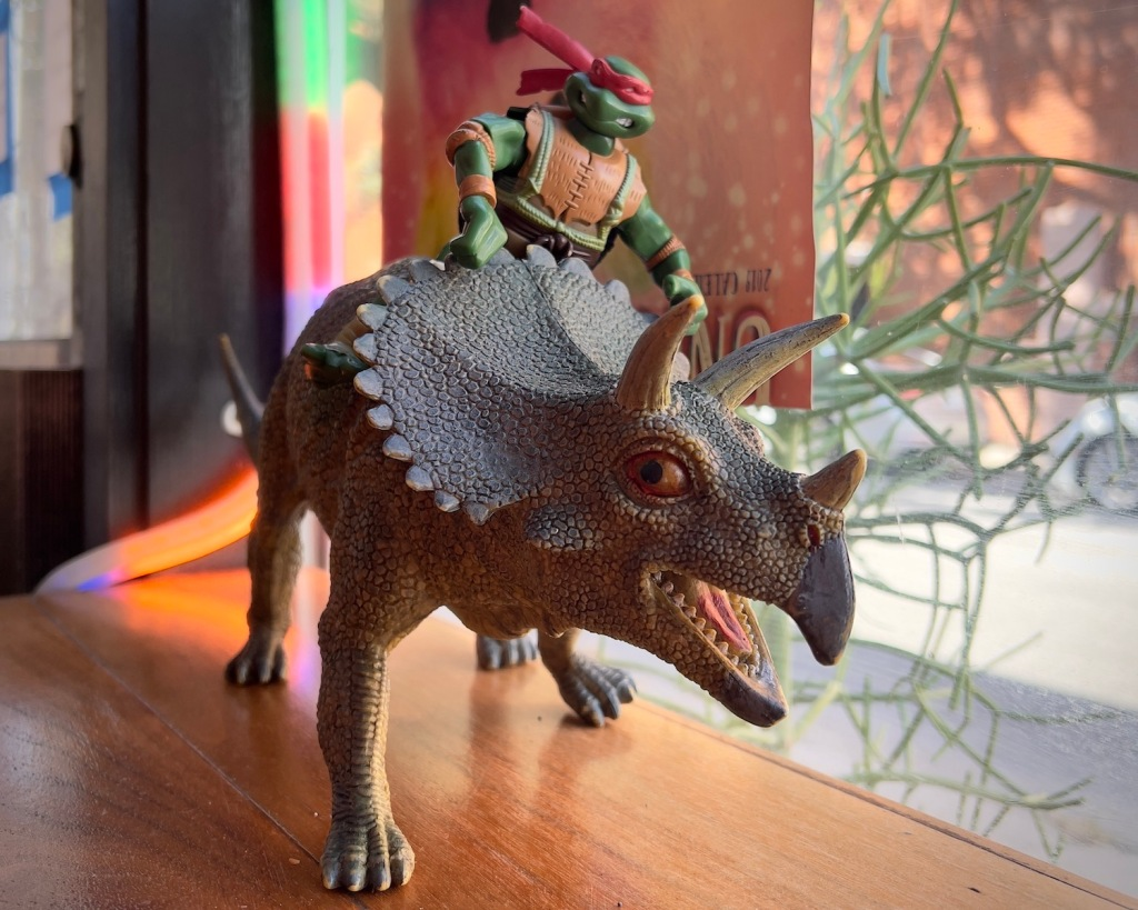 A toy Raphael the Teenage Mutant Ninja Turtle riding a triceratops toy.