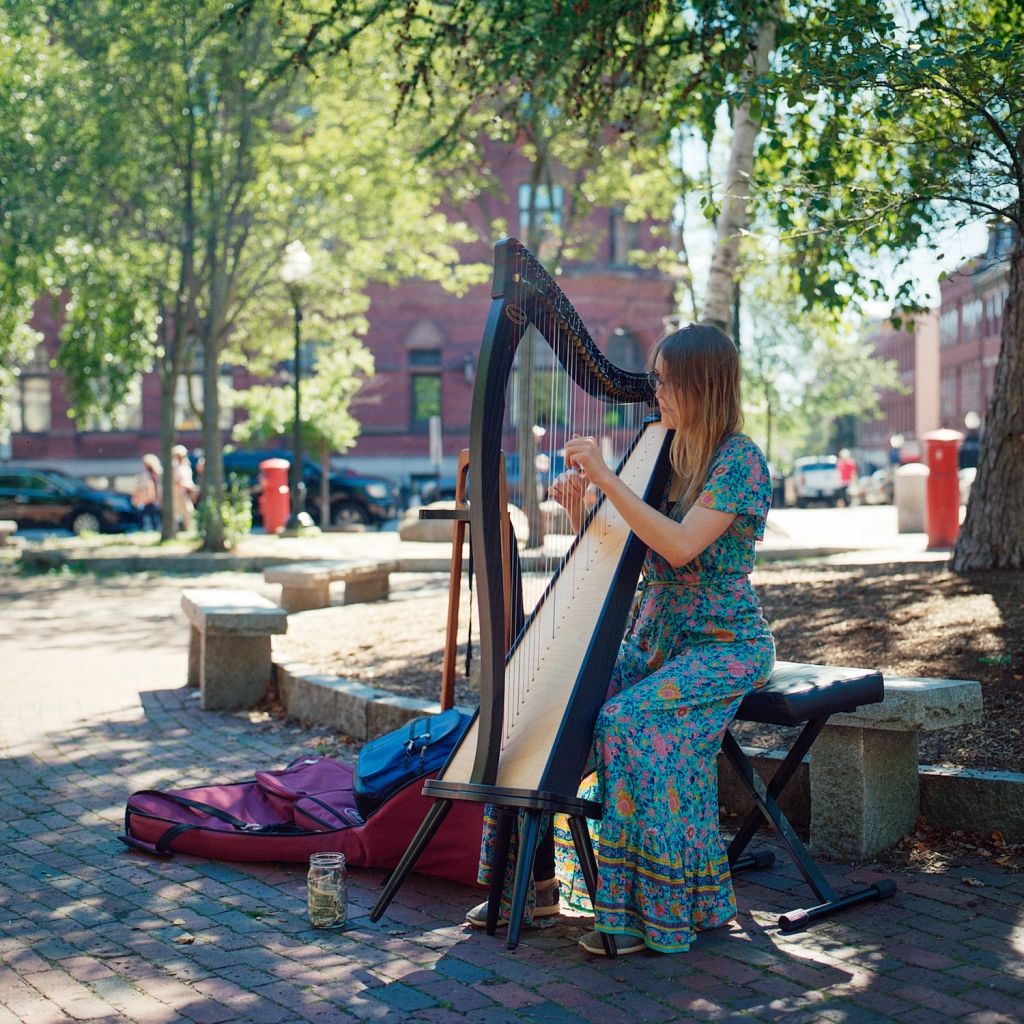 A busker plays a harp in Post Office Park in Portland, ME.