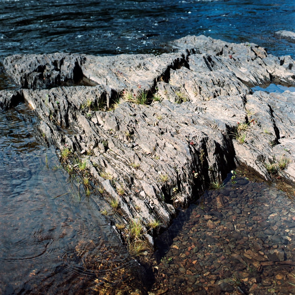 triangular, vertical slate formations in a river bed