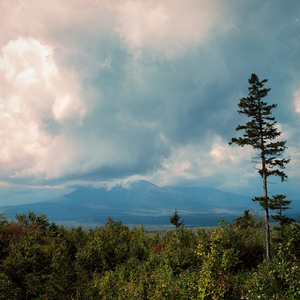Mount Katahdin with its peak in storm clouds viewed from the Katahdin Woods & Waters picnic area
