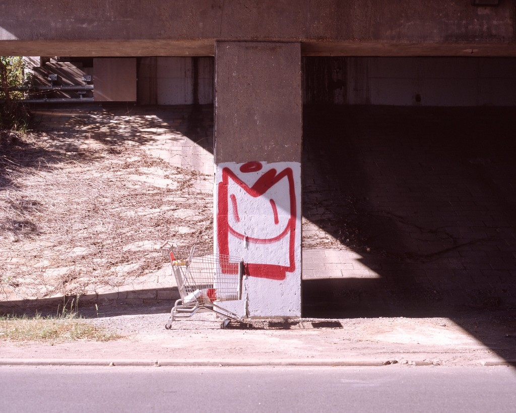 a shopping cart sits in front of a graffitied pillar beneath the I-95 overpass on Overbrook Road.